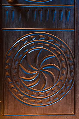 A pattern carved into wood reflects blue and orange light.