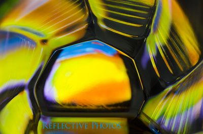 An abstract painting shines through the bottom of a glass and creates colorful reflections along the ridged sides.