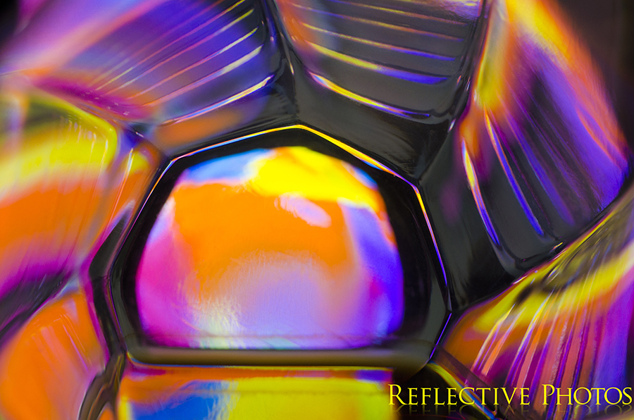 Neon colors make up this sunrise resembling photograph. An abstract painting shines through the bottom of a glass and creates colorful reflections along the ridged sides.