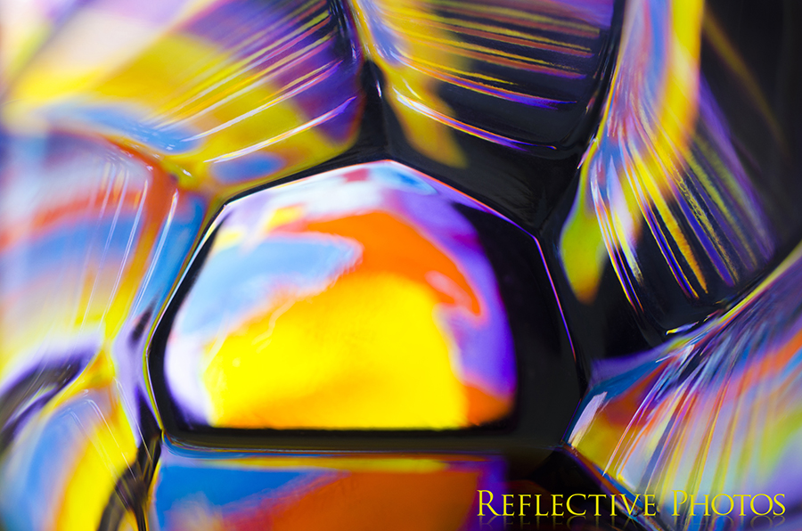 An abstract painting shines through the bottom of a glass and creates colorful reflections along the ridged sides. The resulting photograph resembles a sun with twisting rays.