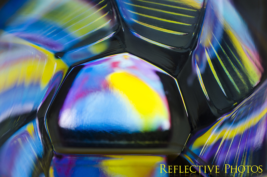 An abstract painting shines through the bottom of a glass and creates colorful reflections along the ridged sides. The cool colors remind me of a winter sunrise.